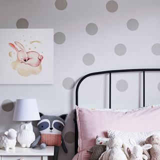 A canvas print above a nightstand beside a child's bed.