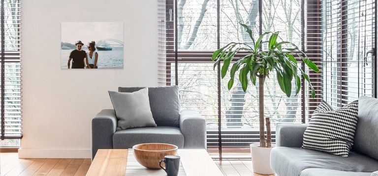 A canvas print hanging above a chair in a living room.
