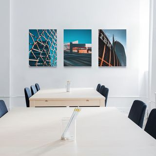 Three canvas prints above two meeting tables.