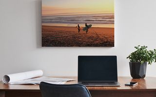 A canvas print positioned above a desk with a laptop.