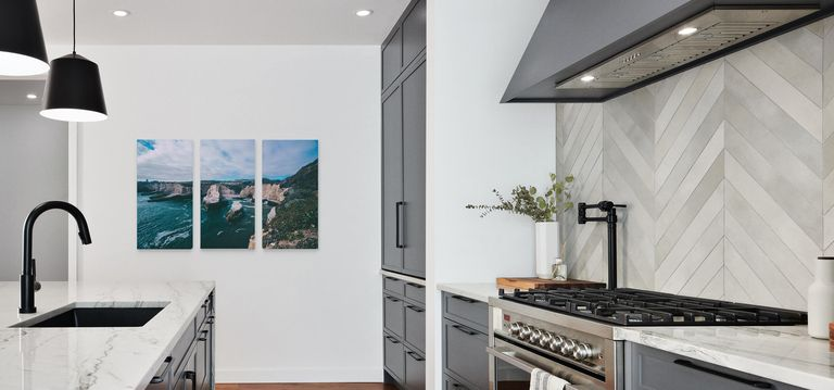 A triptych print hanging in a modern kitchen.
