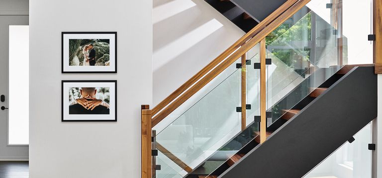 Two framed prints hanging on a wall next to a stair case.