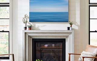 A canvas print positioned above a fireplace.
