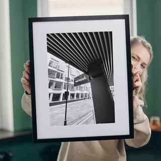 Lady holding up a black and white framed print.