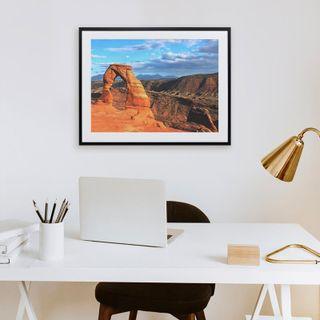 A framed print hanging above a computer desk.