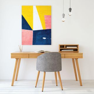 A canvas print hanging above a reading desk.