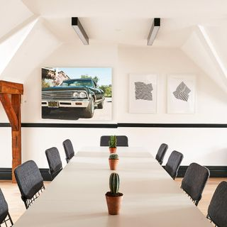 A large canvas print and two framed prints positioned at the end of a long table.