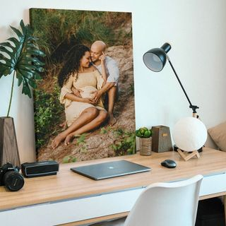 A canvas print on top of a computer desk.
