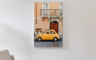 A canvas print of a small yellow car above a side table.
