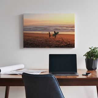 A canvas print positioned above a desk with a laptop