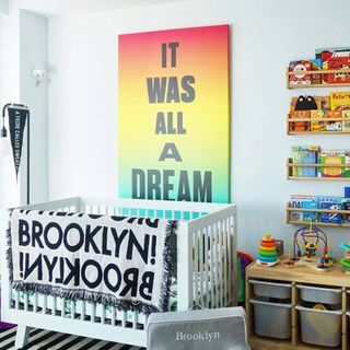 A large, colorful canvas print behind a crib.